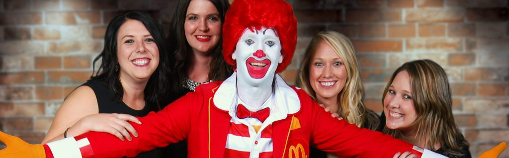 Ronald McDonald with arms wide and four women behind him