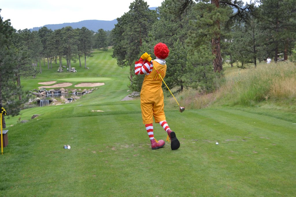 Ronald McDonald hitting from the tee box