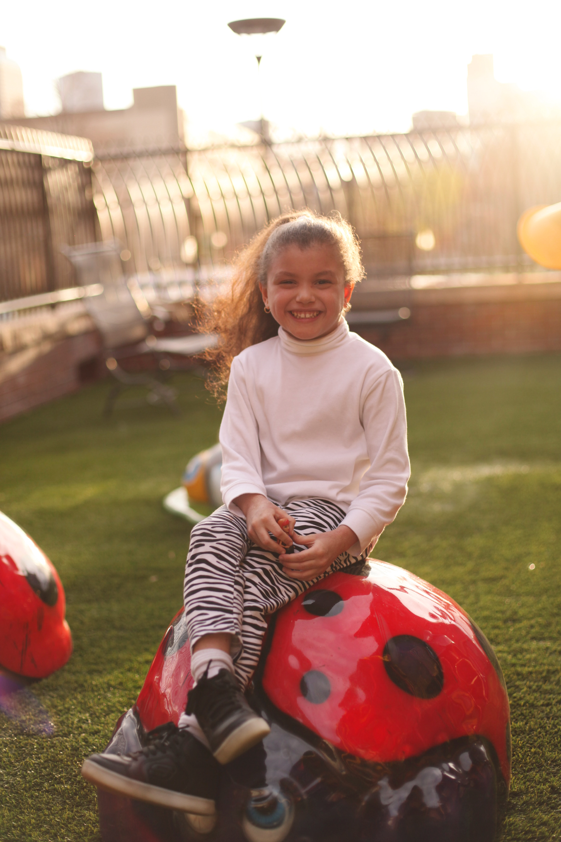 Young smiling girl sitting on a ladybug on the playground