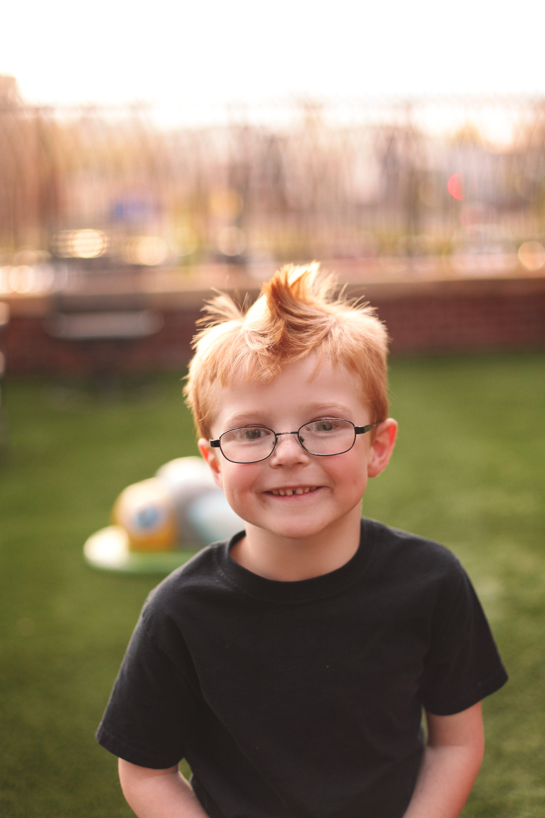 Red-haired boy in glasses smiling on the Ronald McDonald House playground