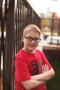 Smiling teen boy leaning on the fence at Ronald McDonald House