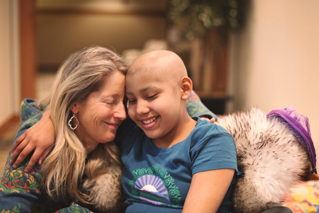 Mom and daughter with cancer resting their heads on each other