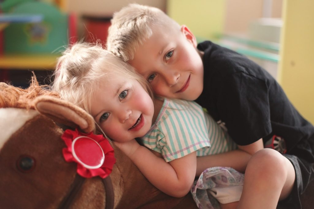 Brother and sister hugging while sitting on a stuffed horse